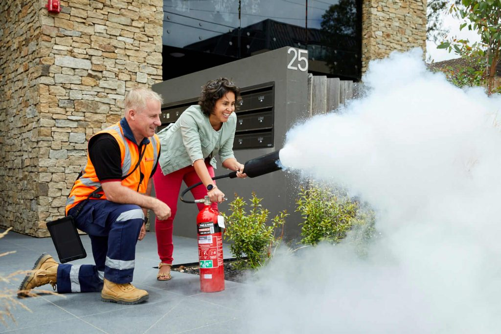 A Fire and Wire technician shows a building resident how to use a fire extinguisher