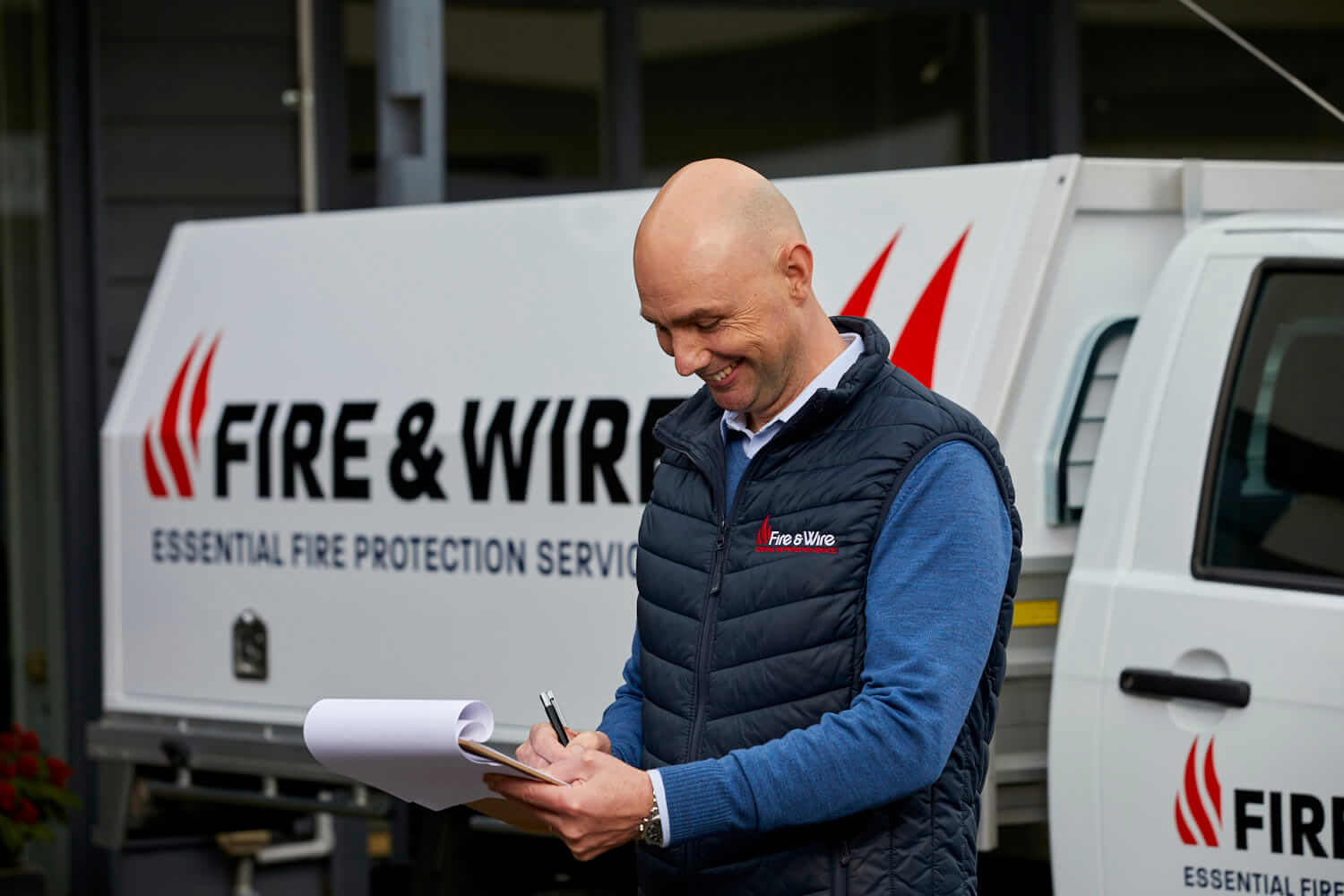 A Fire and Wire employee makes notes on a clipboard, standing in front of a Fire and Wire work vehicle