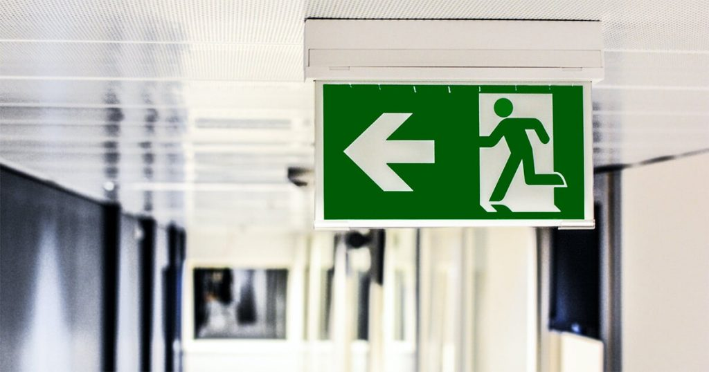 Green emergency exit sign on a building corridor ceiling