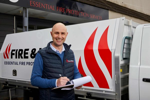 A member of the Fire and Wire fire safety training team stands in front of a company vehicle with a clipboard