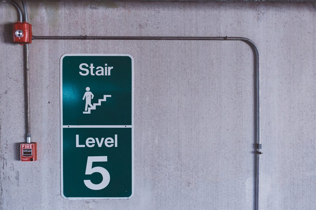 A green level 5 sign in a building fire stairway