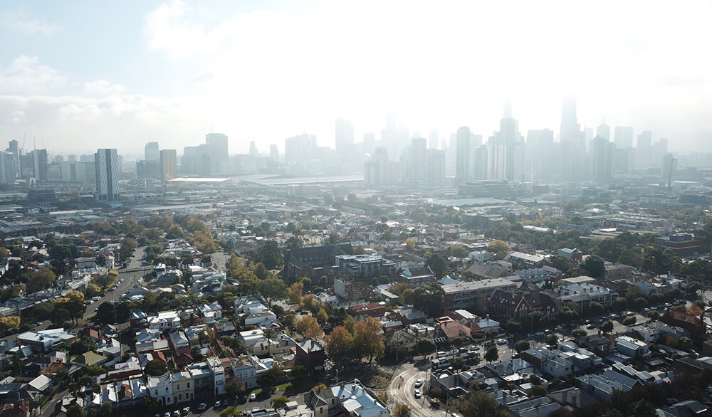 A birds-eye image of Melbourne's city high-rises, with fog rolling in