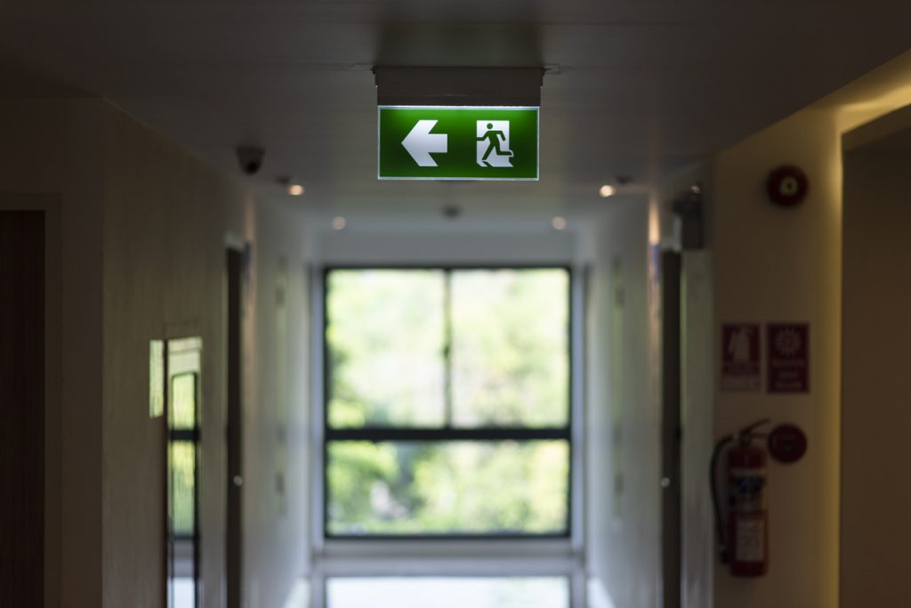 An illuminated emergency exit sign on an office building ceiling