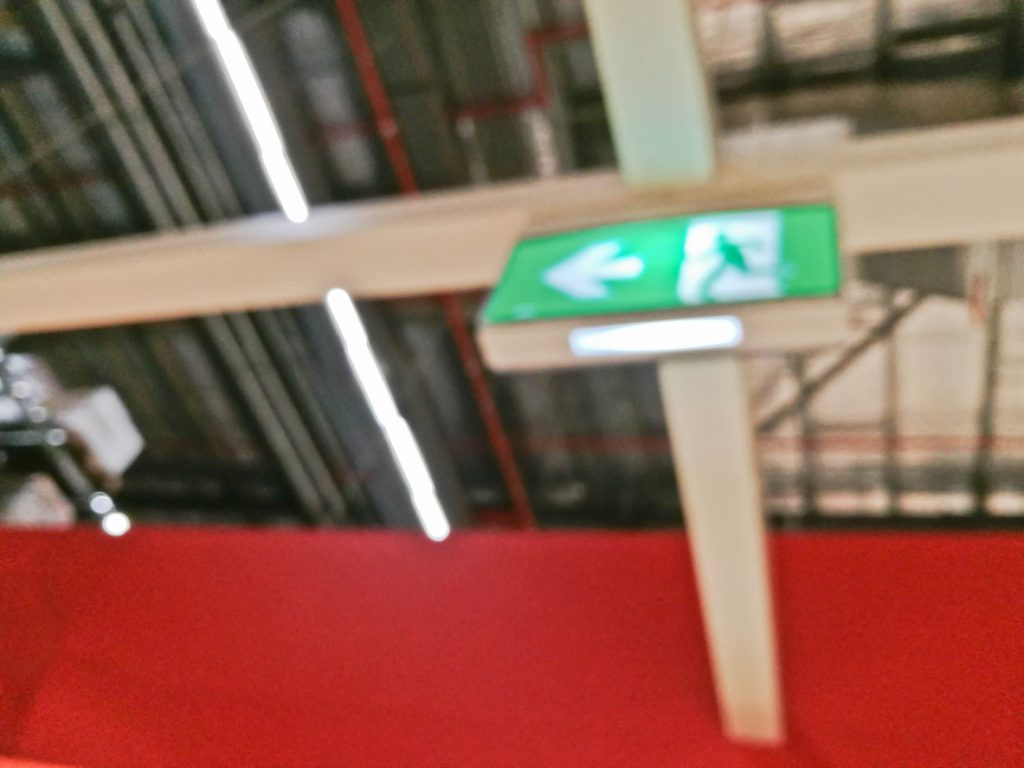 A green, illuminated emergency exit sign affixed to a warehouse ceiling