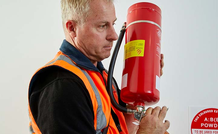A Fire & Wire service technician holds a red fire extinguisher during a scheduled service.
