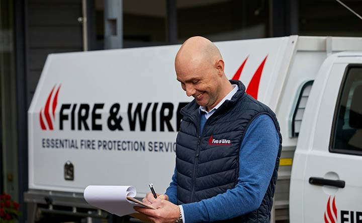 A Fire & Wire employee makes notes on a clipboard, standing in front of a Fire & Wire work vehicle